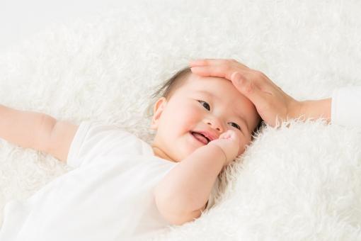 赤ちゃんの頭をなぜるママの手