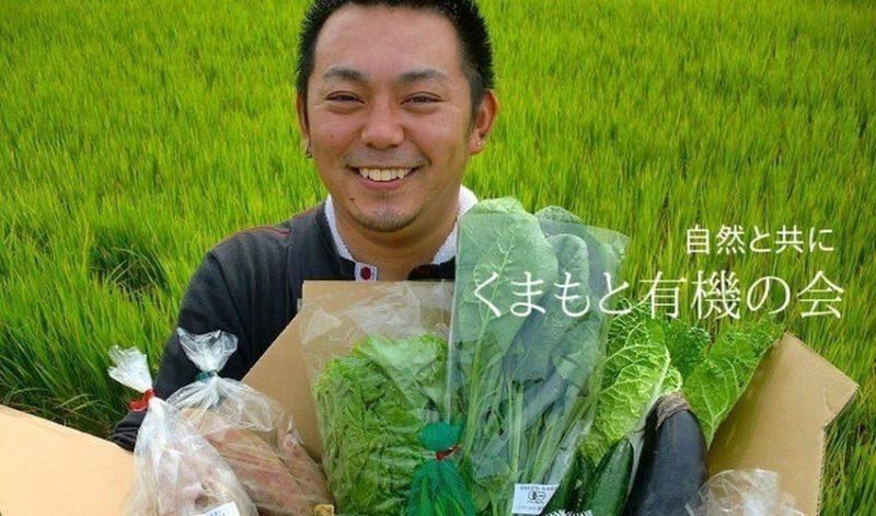 くまもと有機の会 ホームページより 田んぼの前で野菜セットを持って微笑む生産者