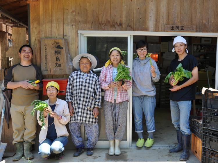 出荷場の前に笑顔で並ぶ桐島畑の生産者たち