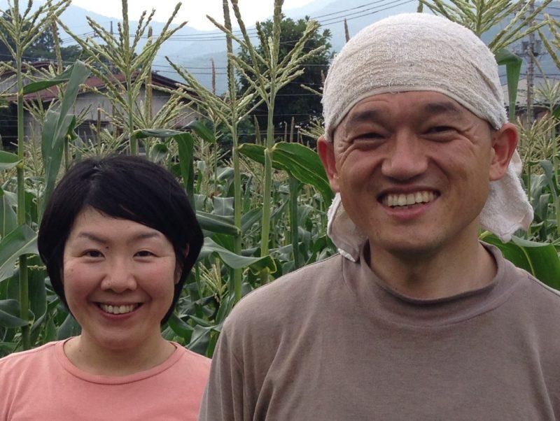 わっパファームホームページより とうもろこし畑の前でほほ笑む農園夫婦