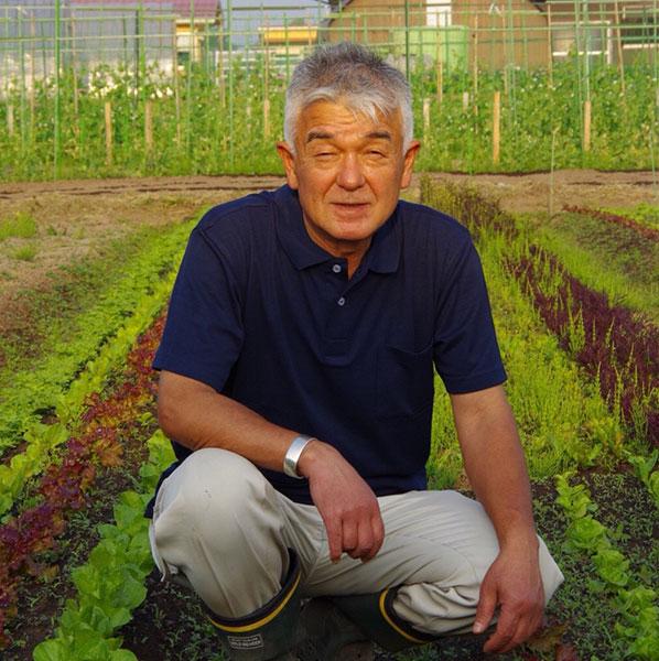 畑でかがむ楽笑農園カームガーデン農園主の画像
