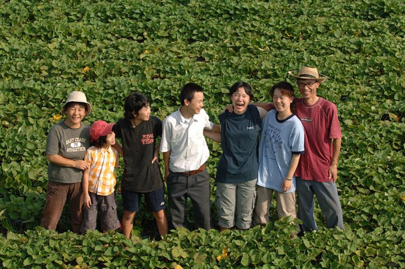 さつまいも畑の真ん中でほほ笑む山脇農園のスタッフ