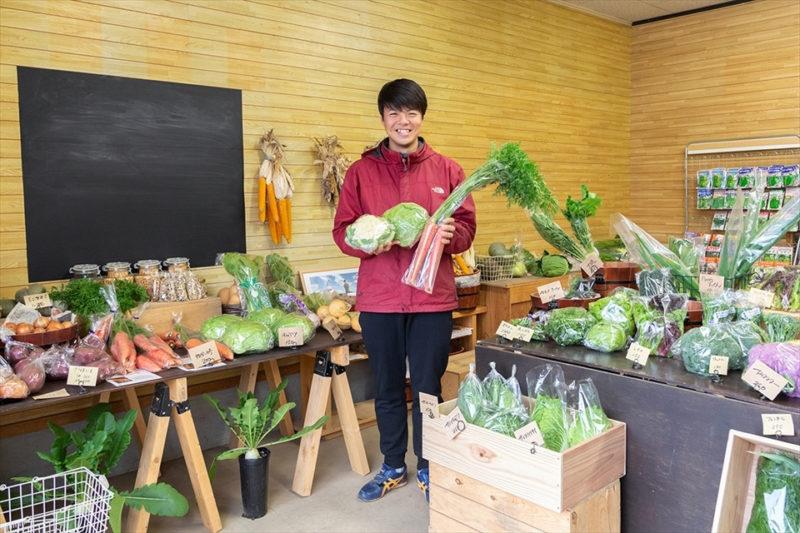 鈴木農場・伊東種苗店ホームページより 店頭で野菜を手にほほえむ4代目店主の画像